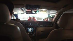 Geschäftsmann, der Luxusauto am Parkplatz im Gebäude, Ansicht vom Rücksitz fährt stock video
