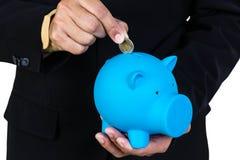 Geschäftsmann, der Münze in blaues Sparschwein setzt Lizenzfreie Stockfotos
