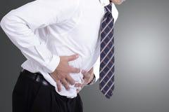 Geschäftsmann, der Magen für Show seine Magenschmerzen hält Lizenzfreie Stockfotografie