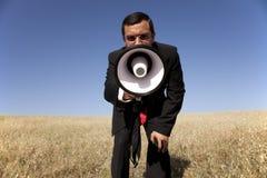 Geschäftsmann, der am Megaphon zu Ihnen schreit Stockbild