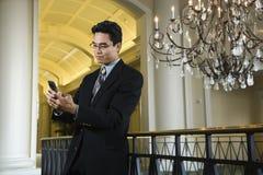 Geschäftsmann, der Meldungen auf Mobiltelefon überprüft Lizenzfreie Stockfotos