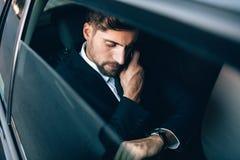 Geschäftsmann, der mit dem Auto reist, Zeit überprüfend und auf cellp sprechend Lizenzfreie Stockbilder