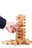 Geschäftsmann, der mit dem hölzernen Spiel (jenga, spielt) auf weißem backgro Stockbilder