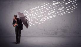 Geschäftsmann, der mit dem Regenschirm und gezogenen Pfeilen schlagen ihn steht Lizenzfreie Stockfotografie