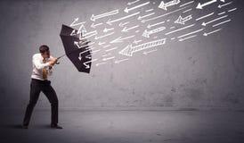 Geschäftsmann, der mit dem Regenschirm und gezogenen Pfeilen schlagen ihn steht Stockfotos