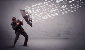 Geschäftsmann, der mit dem Regenschirm und gezogenen Pfeilen schlagen ihn steht Stockfotografie