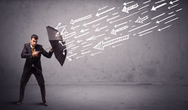 Geschäftsmann, der mit dem Regenschirm und gezogenen Pfeilen schlagen ihn steht Stockbild