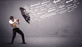 Geschäftsmann, der mit dem Regenschirm und gezogenen Pfeilen schlagen ihn steht Lizenzfreie Stockfotos