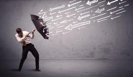 Geschäftsmann, der mit dem Regenschirm und gezogenen Pfeilen schlagen ihn steht Lizenzfreies Stockbild