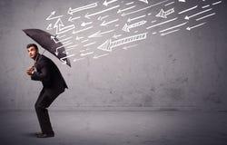 Geschäftsmann, der mit dem Regenschirm und gezogenen Pfeilen schlagen ihn steht Stockbilder