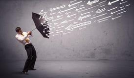 Geschäftsmann, der mit dem Regenschirm und gezogenen Pfeilen schlagen ihn steht Stockfoto