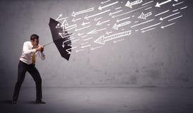 Geschäftsmann, der mit dem Regenschirm und gezogenen Pfeilen schlagen ihn steht Lizenzfreie Stockbilder