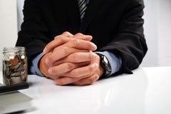 Geschäftsmann, der mit dem Schauen und beim Denken gesorgt an die Planung sitzt Stockfotografie