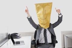 Geschäftsmann, der mit dem smiley gezeichnet auf Papiertüte über Gesicht im Büro zujubelt Stockbilder