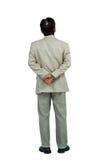 Geschäftsmann, der mit den Händen hinten zurück steht und schaut Stockfotografie