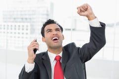 Geschäftsmann, der mit der geballten Faust zujubelt, wie er oben schaut Lizenzfreie Stockfotos