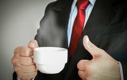 Geschäftsmann, der mit der roten Bindung trinkt einen Tasse Kaffee lächelt Stockfoto