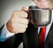 Geschäftsmann, der mit der roten Bindung trinkt einen Tasse Kaffee lächelt Lizenzfreie Stockbilder