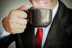 Geschäftsmann, der mit der roten Bindung trinkt einen Tasse Kaffee lächelt Stockbilder