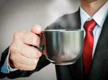 Geschäftsmann, der mit der roten Bindung trinkt einen Tasse Kaffee lächelt Lizenzfreies Stockfoto