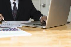 Geschäftsmann, der mit Diagrammschreibarbeitsdokument, Laptopbaut. arbeitet Lizenzfreie Stockbilder