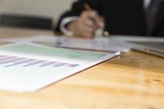 Geschäftsmann, der mit Diagrammschreibarbeitsdokument, Laptopbaut. arbeitet Stockfoto