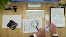 Geschäftsmann, der mit Dokumenten an der Finanzbüro-Ebenen-Lage arbeitet stock video footage