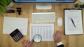 Geschäftsmann, der mit Dokumenten an der Finanzbüro-Ebenen-Lage arbeitet stock video