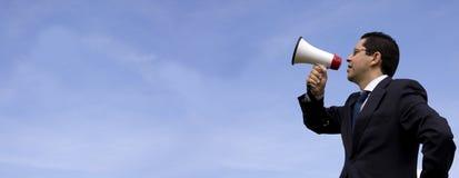 Geschäftsmann, der mit einem Megaphon spricht Stockfotografie