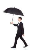 Geschäftsmann, der mit einem Regenschirm geht Stockfotos
