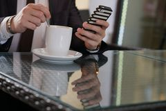 Geschäftsmann, der mit einem Tasse Kaffee und einem Telefon an einem schwarzen Tisch mit einer Reflexion sitzt lizenzfreie stockbilder