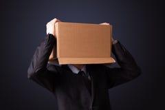Geschäftsmann, der mit einer Pappschachtel auf seinem Kopf gestikuliert Lizenzfreie Stockbilder