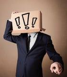 Geschäftsmann, der mit einer Pappschachtel auf seinem Kopf mit Excl gestikuliert Stockfotos