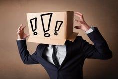 Geschäftsmann, der mit einer Pappschachtel auf seinem Kopf mit Excl gestikuliert Lizenzfreies Stockbild
