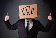 Geschäftsmann, der mit einer Pappschachtel auf seinem Kopf mit Excl gestikuliert Lizenzfreies Stockfoto