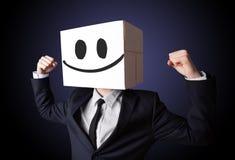 Geschäftsmann, der mit einer Pappschachtel auf seinem Kopf mit smil gestikuliert Lizenzfreie Stockbilder