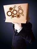 Geschäftsmann, der mit einer Pappschachtel auf seinem Kopf mit Sporn gestikuliert Lizenzfreie Stockfotografie