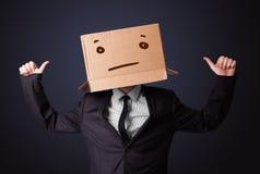 Geschäftsmann, der mit einer Pappschachtel auf seinem Kopf mit stra gestikuliert Lizenzfreie Stockbilder
