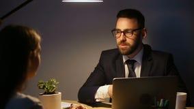 Geschäftsmann, der mit der Frau, verhandelnd mit Kundenhändeschütteln über Schreibtisch spricht stock footage