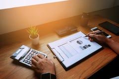 Geschäftsmann, der mit Gewinn- und Verlustrechnung Dokument auf der hölzernen Tabelle arbeitet Die goldene Taste oder Erreichen f stockbilder