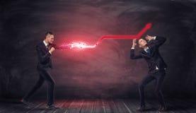 Geschäftsmann, der mit glühendem rotem Pfeil in der Luft schlagen und ein anderer unter ihm Lizenzfreie Stockfotos