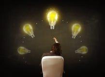 Geschäftsmann, der mit Glühlampen über seinem Kopf sitzt Lizenzfreie Stockfotografie