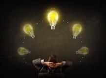 Geschäftsmann, der mit Glühlampen über seinem Kopf sitzt Stockfotografie