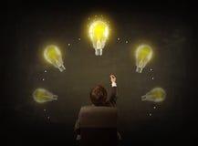 Geschäftsmann, der mit Glühlampen über seinem Kopf sitzt Lizenzfreies Stockfoto