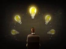 Geschäftsmann, der mit Glühlampen über seinem Kopf sitzt Lizenzfreie Stockfotos