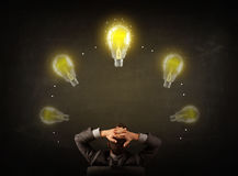 Geschäftsmann, der mit Glühlampen über seinem Kopf sitzt Stockfoto
