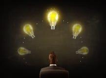 Geschäftsmann, der mit Glühlampen über seinem Kopf sitzt Stockbilder