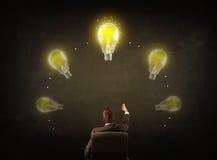 Geschäftsmann, der mit Glühlampen über seinem Kopf sitzt Lizenzfreie Stockbilder