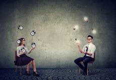 Geschäftsmann, der mit Glühlampen der Idee mit Leitungszeit und Leistungsfähigkeit der Geschäftsfrau jongliert stockfotografie