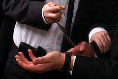 Geschäftsmann, der mit Handschellen gefesselt wird Lizenzfreie Stockfotos